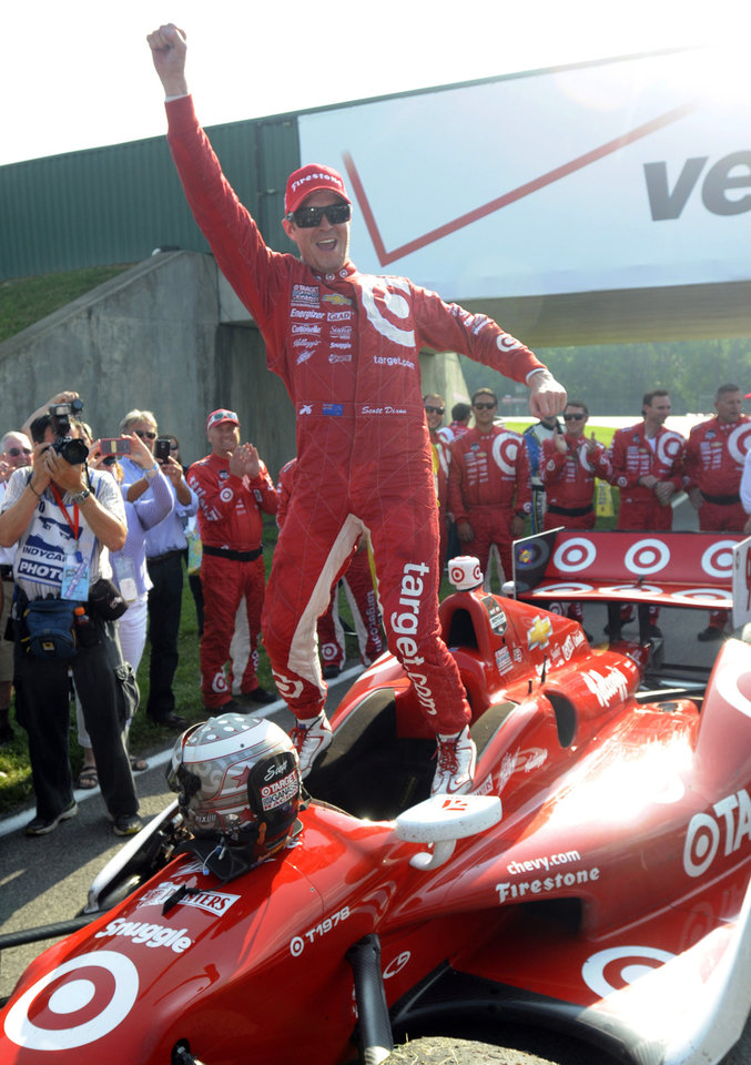 Photo - Scott Dixon, of New Zealand, celebrates standing on his car after winning the IndyCar Honda Indy 200 auto racing at Mid-Ohio Sports Car Course in Lexington, Ohio Sunday, Aug. 3, 2014. Dixon won the race from the last starting place on the grid. (AP Photo/Tom E. Puskar)