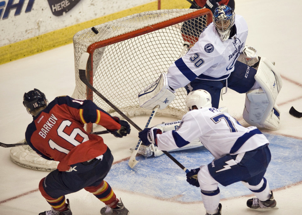 Photo - Tampa Bay Lightning's Ondrej Palat, right front, helps defend the net as goalie Ben Bishop (30) deflects a shot from Florida Panthers' Aleksander Barkov (16) during the second period of an NHL preseason hockey game Thursday, Sept. 26, 2013 in Estero, Fla. (AP Photo/Steve Nesius)