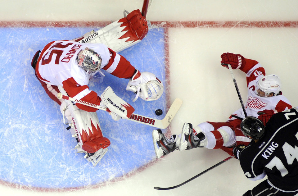 Photo - Detroit Red Wings goalie Jimmy Howard, right, stops a shot by Los Angeles Kings left wing Dwight King, right, as left wing Henrik Zetterberg, of Sweden, falls during the first period of an NHL hockey game, Saturday, Jan. 11, 2014, in Los Angeles. (AP Photo/Mark J. Terrill)