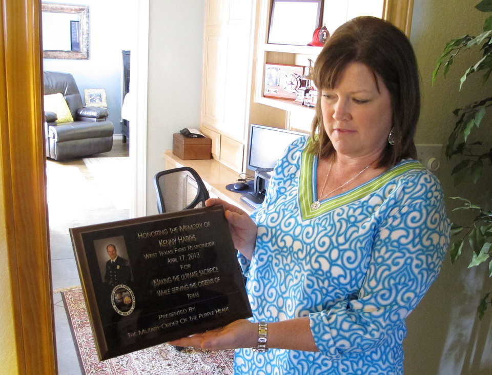 Photo - In this April 9, 2014 photo Holly Harris holds a plaque honoring her husband, Dallas Fire-Rescue Capt. Kenneth Luckey Harris, in her home outside West, Texas, on Tuesday, April 9, 2014. Kenneth Harris was one of 15 people killed in a deadly explosion at West Fertilizer Co., that still raises questions in the community one year later about what happened. (AP Photo/Nomaan Merchant)