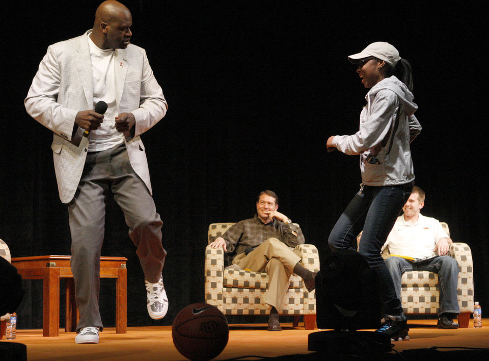 Photo - Former NBA star Shaquille O'Neal dances on stage with Oklahoma State junior Na'Quirah Wallace as OSU basketball coach Travis Ford and OSU basketball player Keiton Page watch during a question and answer session at Gallagher-Iba Arena on the campus of Oklahoma State University in Stillwater, Okla., Tuesday, April 3, 2012. Oklahoma State University's Student Government Association Speakers Board hosted the event. Photo by Bryan Terry, The Oklahoman