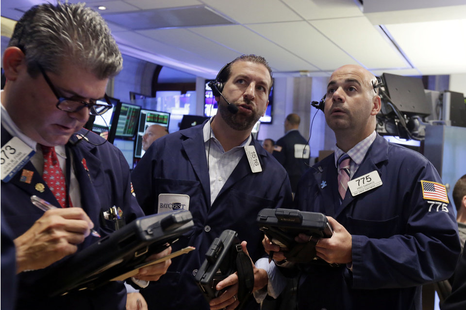 Photo - Trader John Panin, Greg Mulligan, and Fred DeMarco, left to right, work on the floor of the New York Stock Exchange, Friday, June 20, 2014. Stocks are slightly higher in early trading as the market heads for a week of solid gains. (AP Photo/Richard Drew)