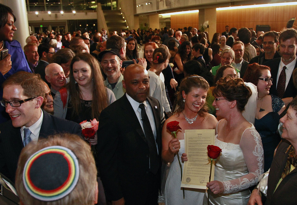 Photo - Just after midnight, Denver Mayor Michael Hancock, center left, stands after performing a civil union vows ceremony for Fran Simon, right, and her partner Anna Simon, at the Webb Municipal Building in Denver, Wednesday May 1, 2013. Fran and Anna Simon were the first to receive a civil union certificate.  In March 2013, the Colorado General Assembly passed SB-11, the Colorado Civil Union Act, which provides committed same-sex couples with legal protections and responsibilities. The act went into effect on May 1, 2013. (AP Photo/Brennan Linsley)
