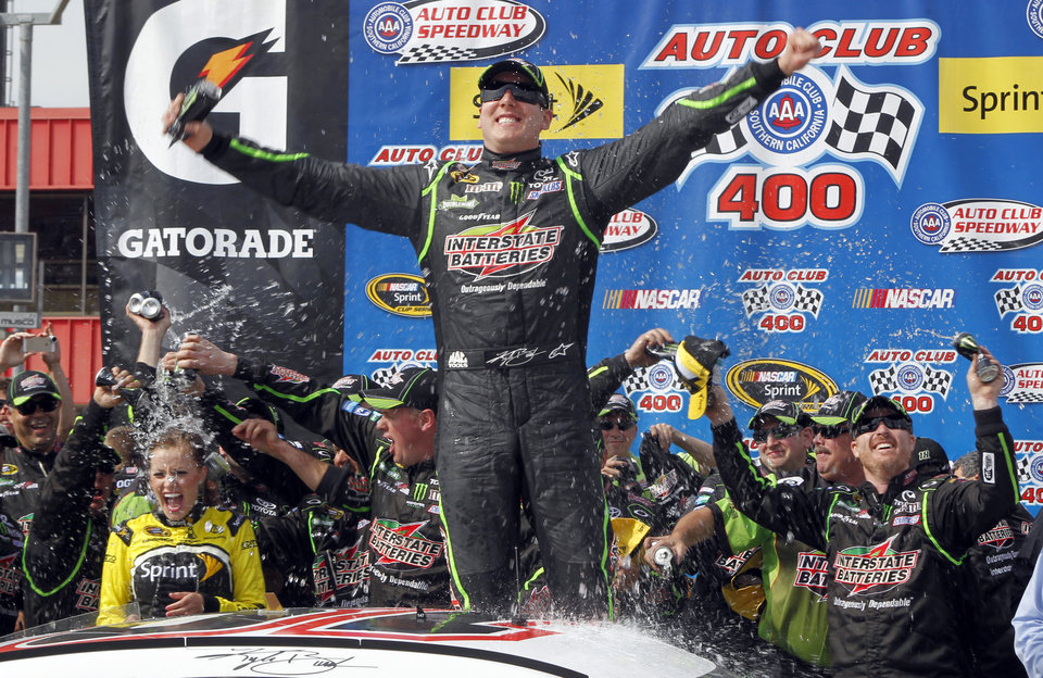 Photo - Kyle Busch, center, celebrates, as the team drenches his wife, Samantha Busch, left, in victory circle after winning the NASCAR Sprint Series auto race in Fontana, Calif., Sunday, March 23, 2014. (AP Photo/Alex Gallardo)