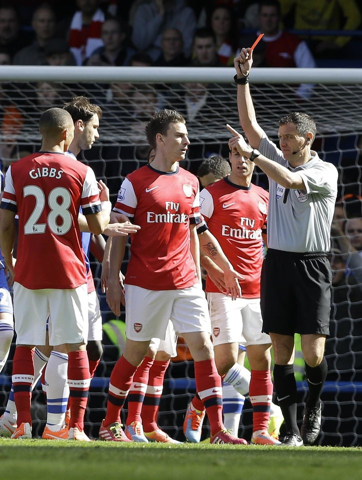 Photo - Arsenal's Kieran Gibbs, left, gets a red card during the English Premier League soccer match between Chelsea and Arsenal at Stamford Bridge stadium in London, Saturday, March 22, 2014. (AP Photo/Kirsty Wigglesworth)