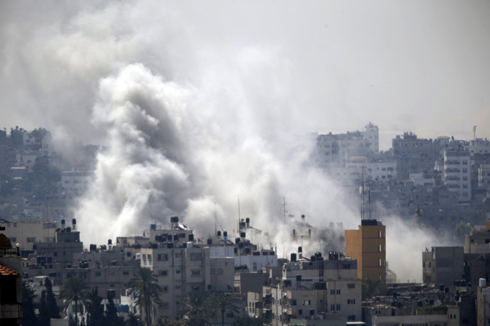 Photo - Smoke from an Israeli strike rises over Gaza City, Wednesday, July 23, 2014. Israeli troops battled Hamas militants on Wednesday near a southern Gaza Strip town, sending Palestinian residents fleeing, as the U.S. secretary of state presses ahead with top-gear efforts to end the conflict that has killed hundreds of Palestinians and tens of Israelis.(AP Photo)