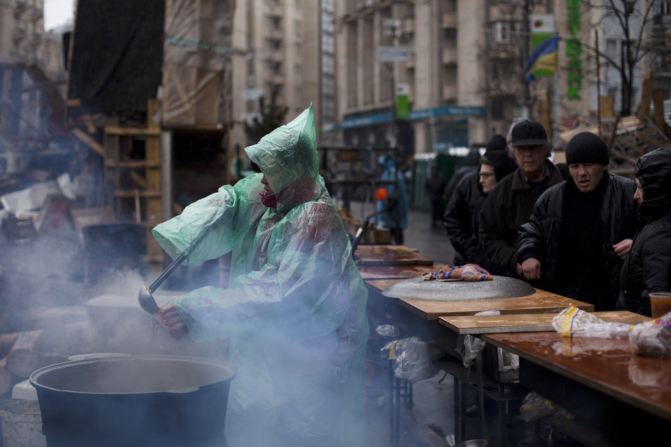Photo - A woman uses a ladle to pour soup into a cup to serve people queuing for free food during a rainfall in Kiev's Independence Square, Ukraine, Sunday, March 16, 2014. In a referendum watched closely around the world, residents in Ukraine's strategic Crimean Peninsula voted Sunday on whether to demand greater autonomy or split off and seek to join Russia. (AP Photo/David Azia)