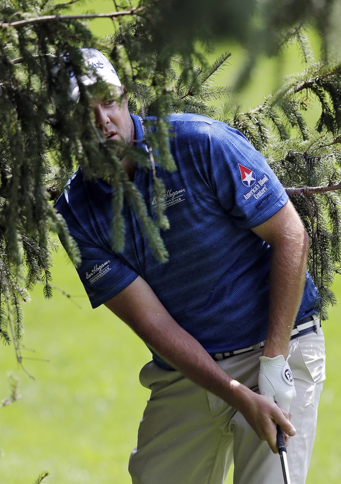 Photo - Marc Leishman, from Australia, hits from a tree to the 18th green during the first round of the Bridgestone Invitational golf tournament Thursday, July 31, 2014, at Firestone Country Club in Akron, Ohio. (AP Photo/Mark Duncan)