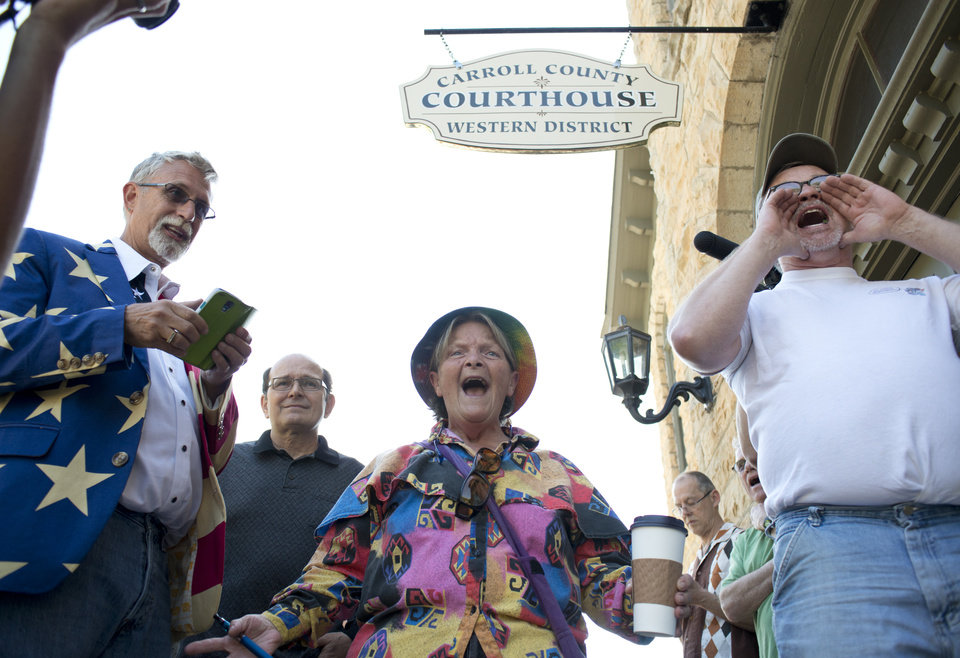 Photo - Sheila McFadden, center, and Ken Riley, right, yell words of encouragement at the crowd gathered in front of the Carroll County Courthouse after initially being turned away for a marriage license in Eureka Springs, Ark., Saturday, May 10, 2014, in Eureka Springs, Ark. Same-sex couples were eventually granted marriage licenses, Saturday, in Eureka Springs after a judge overturned Amendment 83, which banned same-sex marriage in the state of Arkansas. (AP Photo/Sarah Bentham)