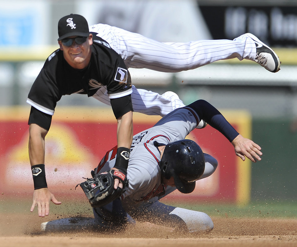 Photo - Chicago White Sox second baseman Gordon Beckham watches his throw to first base after forcing out Atlanta Braves' Freddie Freeman at second base during the second inning of an interleague baseball in Chicago, Saturday, July 20, 2013. (AP Photo/Paul Beaty)