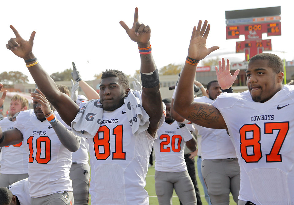 Photo - Oklahoma State Cowboys wide receiver Justin Blackmon (81) and Tracy Moore (87) salute the Cowboy fans after the 66-6 win over Texas Tech in the college football game between the Oklahoma State University Cowboys (OSU) and Texas Tech University Red Raiders (TTU) at Jones AT&T Stadium on Saturday, Nov. 12, 2011. in Lubbock, Texas.  Photo by Chris Landsberger, The Oklahoman  ORG XMIT: KOD
