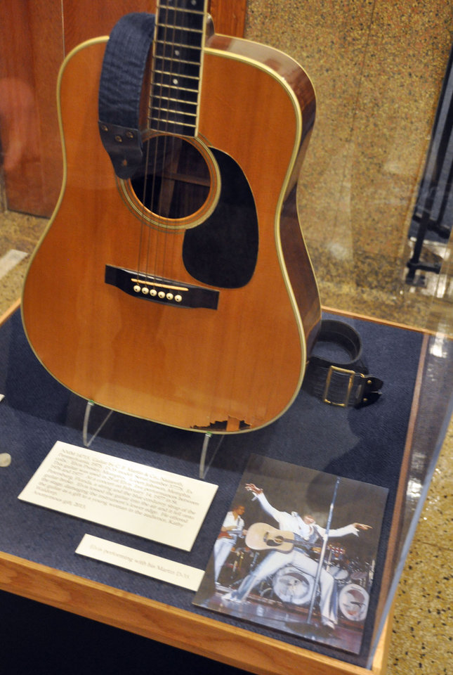 Photo - This April 22, 2013 photo shows a Martin D-35 guitar played by Elvis Presley during the final tour before his death in 1977 at the National Music Museum in Vermillion, S.D. The instrument was donated to the museum by Robert Johnson, a guitarist who played in the 1970s with Isaac Hayes and John Entwistle's Ox. Presley smashed the guitar after a string and the shoulder strap broke during a February 1977 show in St. Petersburg, Fla., and it was given that night to a woman in the audience. (AP Photo/Dirk Lammers)