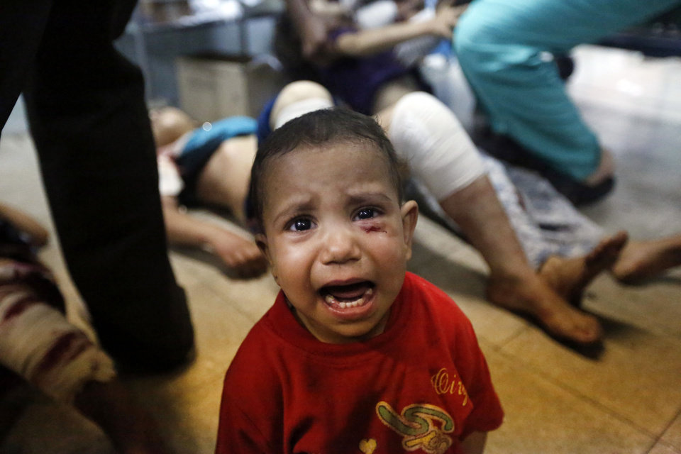 Photo - A Palestinian child, wounded in an Israeli strike on a compound housing a U.N. school in Beit Hanoun, in the northern Gaza Strip, cries at the emergency room of the Kamal Adwan hospital in Beit Lahiya, Thursday, July 24, 2014. Israeli tank shells hit the compound, killing more than a dozen people and wounding dozens more who were seeking shelter from fierce clashes on the streets outside. Gaza health official Ashraf al-Kidra says the dead and injured in the school compound were among hundreds of people seeking shelter from heavy fighting in the area. (AP Photo/Lefteris Pitarakis)