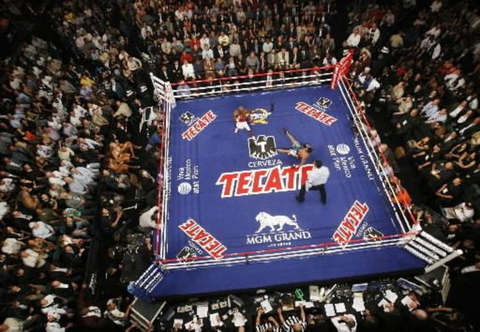 Referee Tony Weeks watches Floyd  Mayweather Jr., upper left, knock down Juan Manuel  Marquez, of Mexico, during their non-title welterweight boxing match in Las Vegas, Saturday, Sept. 19, 2009.  Mayweather won by a unanimous decision. (AP Photo/Isaac Brekken)