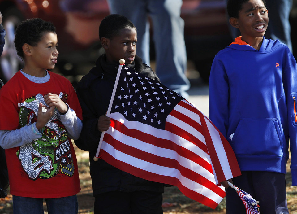 Photo - Boys from Soldier Creek Elementary School stand along Douglas Blvd. to watch the parade as it passes in front of their school. The city of Midwest City teamed with civic leaders and local merchants to display their appreciation for veterans and active military forces by staging a hour-long Veteran's Day parade that stretched more than a mile and a half along three of the city's busiest streets Monday morning, Nov. 12, 2012. Hundreds of people lined the parade route, many of them waving small American flags that had ben distributed by volunteers who marched near the front of the parade. A fly-over performed by F-16s from the138th Fighter Wing, Oklahoma Air National Guard unit in Tulsa thrilled spectators. Five veterans representing military personnel who served in five wars and military actions served as  Grand Marshals for the parade. Leading the parade was the Naval Reserve seven-story American flag, carried by 100 volunteers from First National Bank of Midwest City, Advantage Bank and the Tinker Federal Credit Union. The flag is 50 feet by 76 feet, weighs 110 pounds and was sponsored by the MWC Chapter of Disabled American Veterans. Photo by Jim Beckel, The Oklahoman