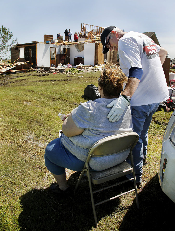 Photo - A man offers support to  Bonnie Meritt as she sits in her front yard while family and friends look for items that can be saved in the home where she and her husband, Kay, lived since 1996.  The home is at 20545 SW 15 in Union City   Bonnie Meritt said nine homes near her, including hers, were damaged or destroyed in Friday night's tornado. The couple was unharmed. They took shelter inside the Union City fire station before the tornado hit. Photo  by Jim Beckel, The Oklahoman.