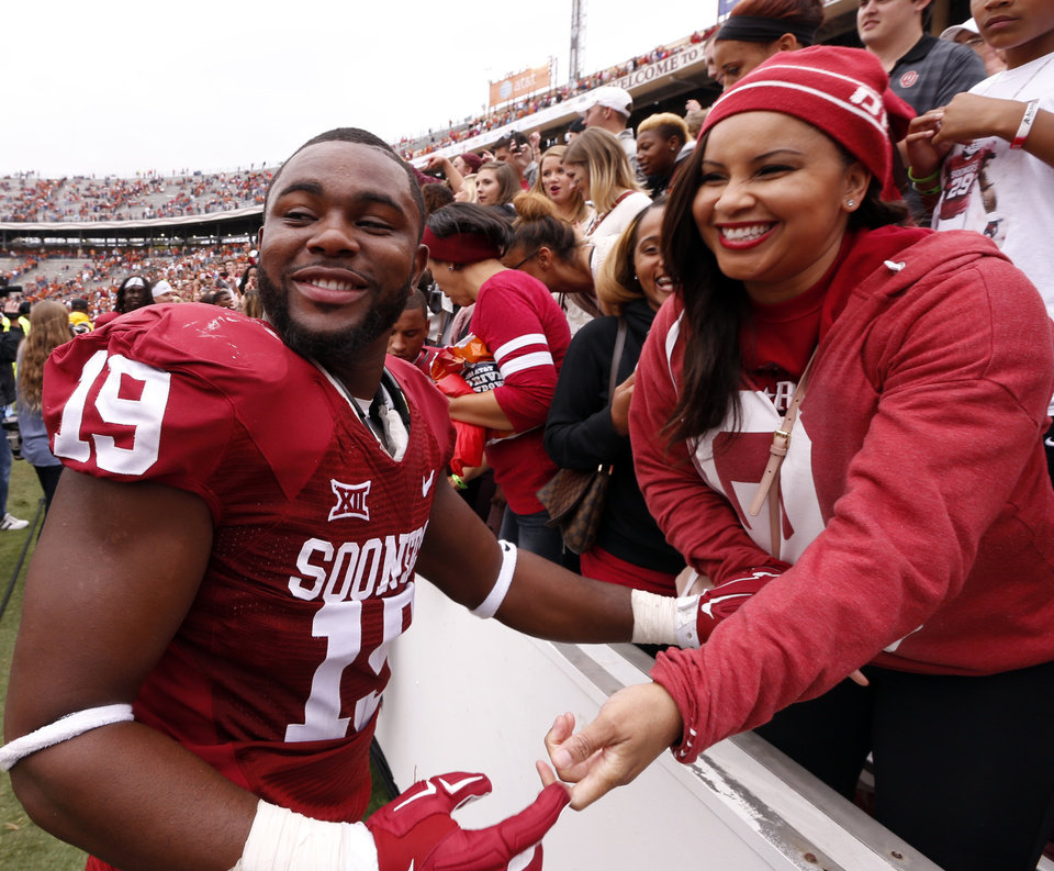 Photo - Oklahoma's Eric Striker (19) is congratulated by his mother Lia Skelton after the Red River Showdown college football game where the University of Oklahoma Sooners (OU) defeated the University of Texas Longhorns (UT)  31-26 at the Cotton Bowl in Dallas, Texas on Saturday, Oct. 11, 2014. 