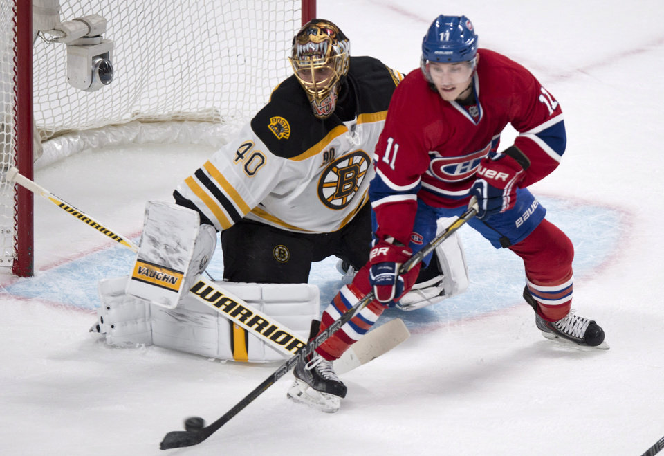 Photo - Montreal Canadiens' Brendan Gallagher tries to deflect a shot past Boston Bruins goalie Tuukka Rask during first period NHL hockey action Thursday, Dec. 5, 2013, in Montreal. (AP Photo/The Canadian Press, Paul Chiasson)