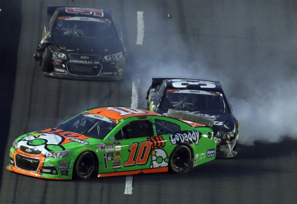 Photo - Danica Patrick (10) spins in front of Brian Scott (33) during the NASCAR Sprint Cup series Coca-Cola 600 auto race at the Charlotte Motor Speedway in Concord, N.C., Sunday, May 25, 2014. (AP Photo/Gerry Broome)