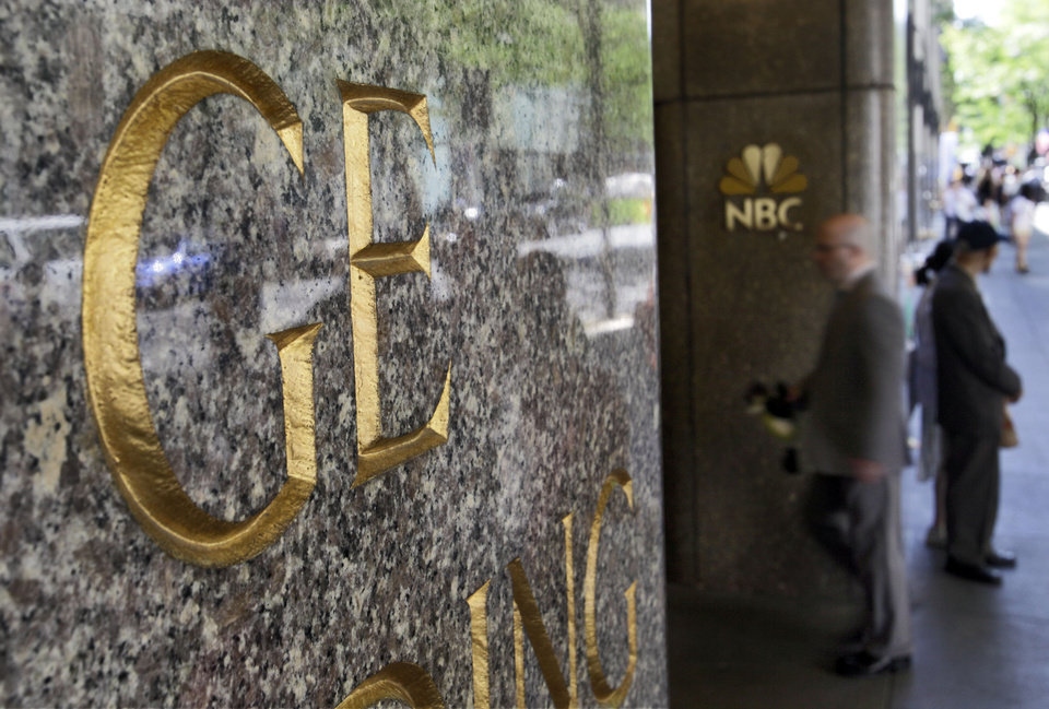 "Photo - FILE - In this file photo made July 15, 2009, General Electric and NBC logos adorn the GE Building in New York's Rockefeller Center. Comcast said Tuesday that it's buying General Electric's 49 percent stake in the NBCUniversal joint venture for $16.7 billion several years early, as the company takes advantage of low borrowing costs and what CEO Brian Roberts called a ""very attractive price."" (AP Photo/Richard Drew, File)"