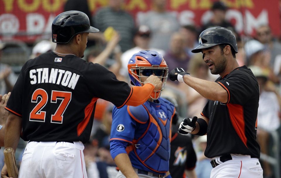 Photo - Miami Marlins' Garrett Jones, right, fist-bumps teammate Giancarlo Stanton after the two scored off Jones' two-run home run in the fourth inning of an exhibition spring training baseball game as New York Mets catcher Travis d'Arnaud, center, looks on, Saturday, March 22, 2014, in Jupiter, Fla. (AP Photo/David Goldman)