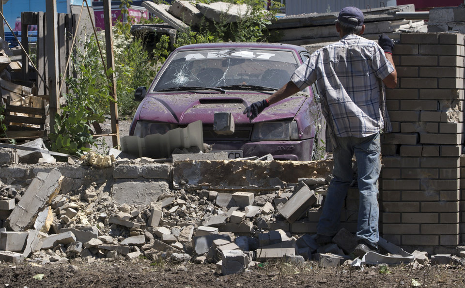 Photo - A man removes debris in a motor depot after shelling in the city of Kramatorsk, Donetsk region, eastern Ukraine Thursday, July 3, 2014. Residential areas came under shelling on Wednesday and Thursday from government forces. (AP Photo/Dmitry Lovetsky)