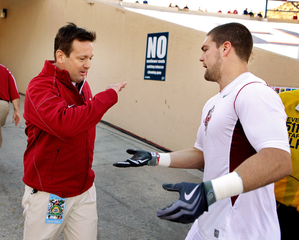Photo - Head coach Bob Stoops encourages players as they head to the locker room during pre-game warms up before the college football game between the University of Oklahoma Sooners (OU) and the Stanford University Cardinal will be played on Thursday, Dec. 31, 2009, in El Paso, Tex.   Photo by Steve Sisney, The Oklahoman