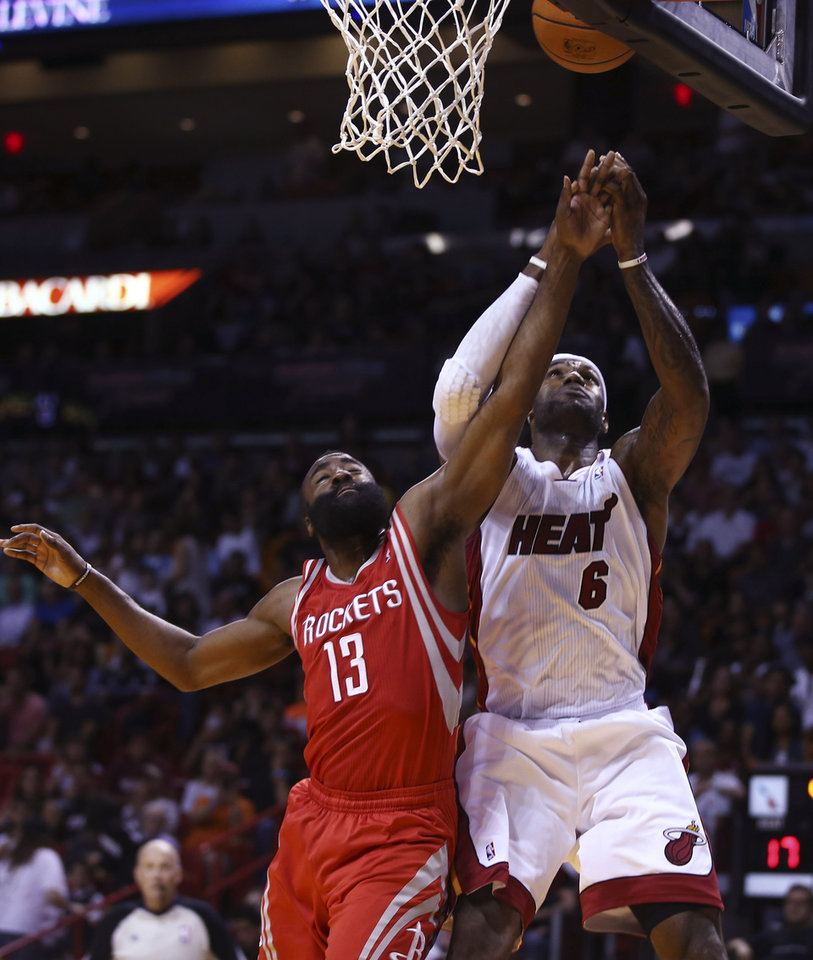 Photo - Houston Rockets' James Harden (13) tries to block Miami Heat's LeBron James (6) during the first half of an NBA  basketball game in Miami, Sunday, March 16, 2014. (AP Photo/J Pat Carter)
