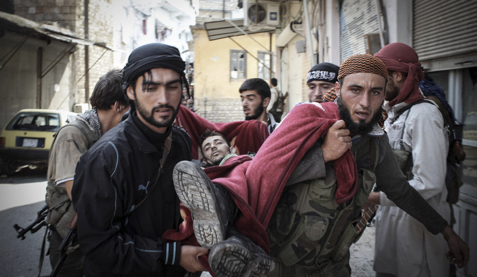 Photo -   In this Tuesday, Oct. 30, 2012 photo, Syrian rebels carry a wounded comrade in a blanket away from the frontline in the town of Harem, Syria. Despite two weeks of attacking a Roman-era citadel in which pro-Assad militia are dug in, the rebels failed to secure the town. (AP Photo/Mustafa Karali)