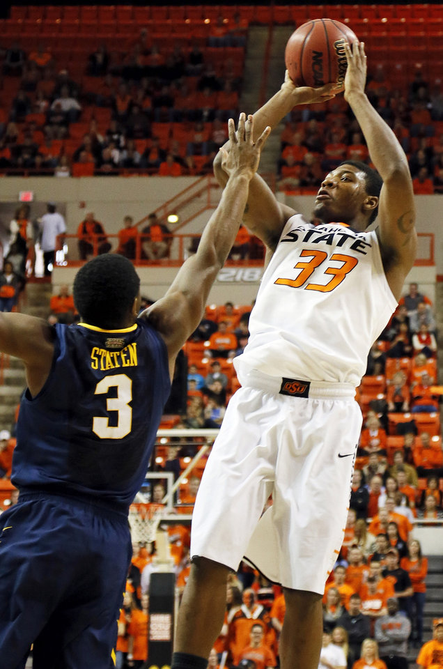 Oklahoma State's Marcus Smart (33) shoots against West Virginia's Juwan Staten (3) during an NCAA college basketball game in Stillwater, Okla., Saturday, Jan. 26, 2013. (AP Photo/The Oklahoman, Nate Billings)