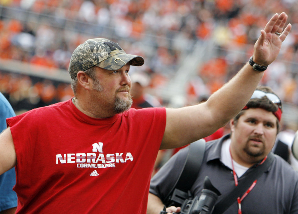 Photo - Nebraska fan and comedian Larry the Cable Guy waves to fans during the college football game between the Oklahoma State Cowboys (OSU) and the Nebraska Huskers (NU) at Boone Pickens Stadium in Stillwater, Okla., Saturday, Oct. 23, 2010. Photo by Nate Billings, The Oklahoman