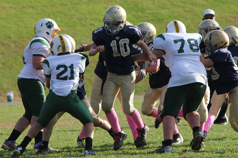 In this 2012 photo provided by Marycecelia Pla, her daughter, Caroline Pla (10), center, plays in a Catholic Youth Organization league football game. The 11-year-old girl who's been playing football since kindergarten wants Philadelphia's Roman Catholic archdiocese to overturn a boys-only rule. (AP Photo/Pla Family)