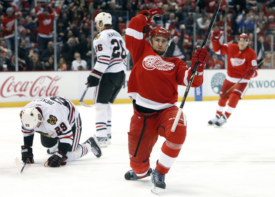 Photo - Detroit Red Wings defenseman Kyle Quincey, right, celebrates his goal against Chicago Blackhawks goalie Corey Crawford in the second period of an NHL hockey game Wednesday, Jan. 22, 2014, in Detroit. (AP Photo/Paul Sancya)