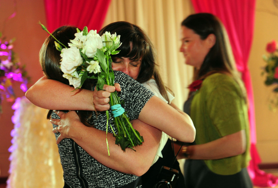 Photo - Julia Fraser hugs a family member after getting married as Jessica Rohrbacher, right, walks behind after get married at the Melody Ballroom in Portland, Ore., on Monday, May 19, 2014. Federal Judge Michael McShane released an opinion on Oregon's Marriage Equality lawsuit that grants gay and lesbian couples the freedom to marry in Oregon.  (AP Photo/Steve Dykes)