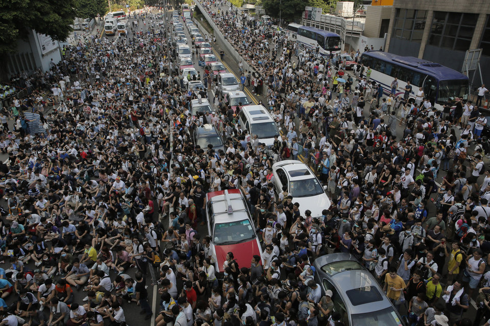 Photo - Thousands of people block a main road in Hong Kong, Sunday, Sept. 28, 2014. Hong Kong activists kicked off a long-threatened mass civil disobedience protest Sunday to challenge Beijing over restrictions on voting reforms, escalating the battle for democracy in the former British colony after police arrested dozens of student demonstrators. (AP Photo/Vincent Yu)