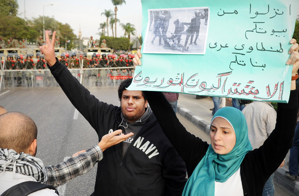 Photo -   An Egyptian woman holds a banner that reads in Arabic,