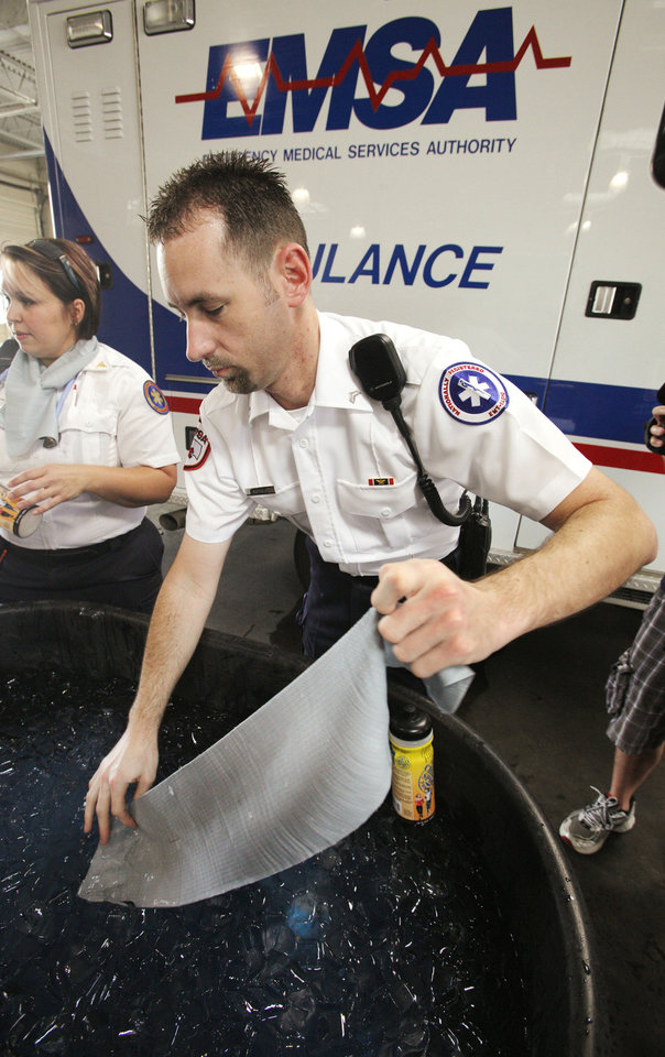 Photo - Chad Hilton, EMSA EMT, removes a Chilly Sport towel from ice water before tying it on at EMSA in Oklahoma City Tuesday, July 10, 2012. EMSA issued the cooling towels to staff to help stay cool during the current heat wave in central Oklahoma. Photo by Paul B. Southerland, The Oklahoman