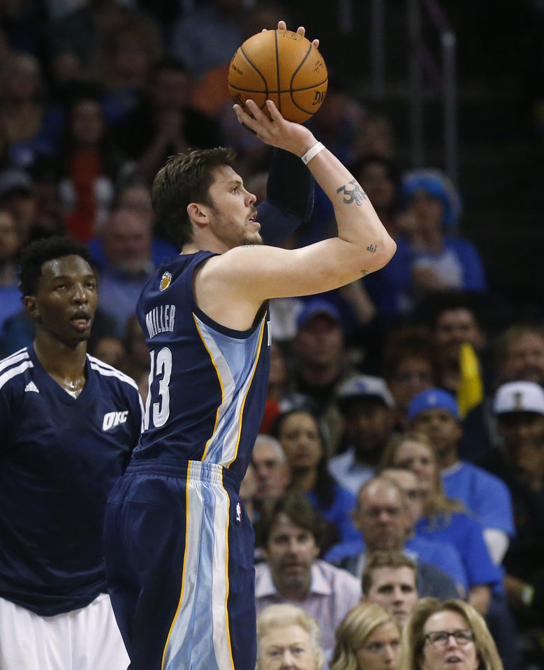 Photo - Oklahoma City Thunder center Hasheem Thabeet, left, watches from the bench as Memphis Grizzlies forward Mike Miller (13) shoots during the fourth quarter of an NBA basketball game in Oklahoma City, Friday, Feb. 28, 2014. Oklahoma City won 113-107. (AP Photo/Sue Ogrocki)