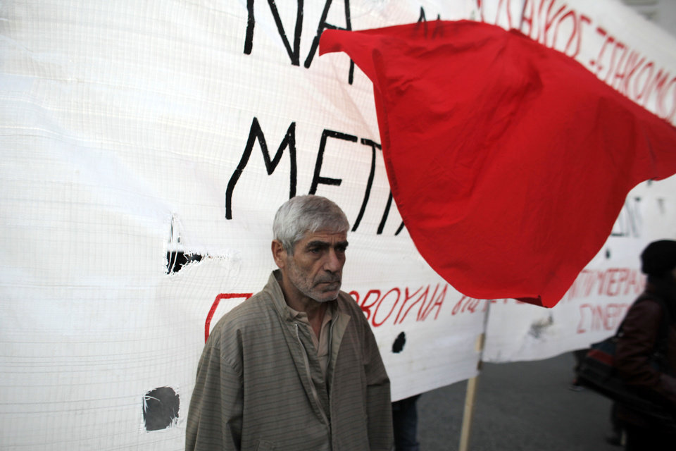 A protester stands in front of a banner during a rally in Athens on Saturday, Nov. 17, 2012. Several thousand marchers are commemorating the 39th anniversary of a deadly student uprising against the then ruling dictatorship, with more than 6,000 police deployed in the center of the Greek capital. (AP Photo/Kostas Tsironis)