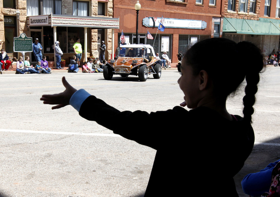 Photo - Six year old Abrielle Wakefield waves to one of the Shriners cars during the 89ers Day Parade in Guthrie, OK, Saturday, April 20, 2013,  By Paul Hellstern, The Oklahoman