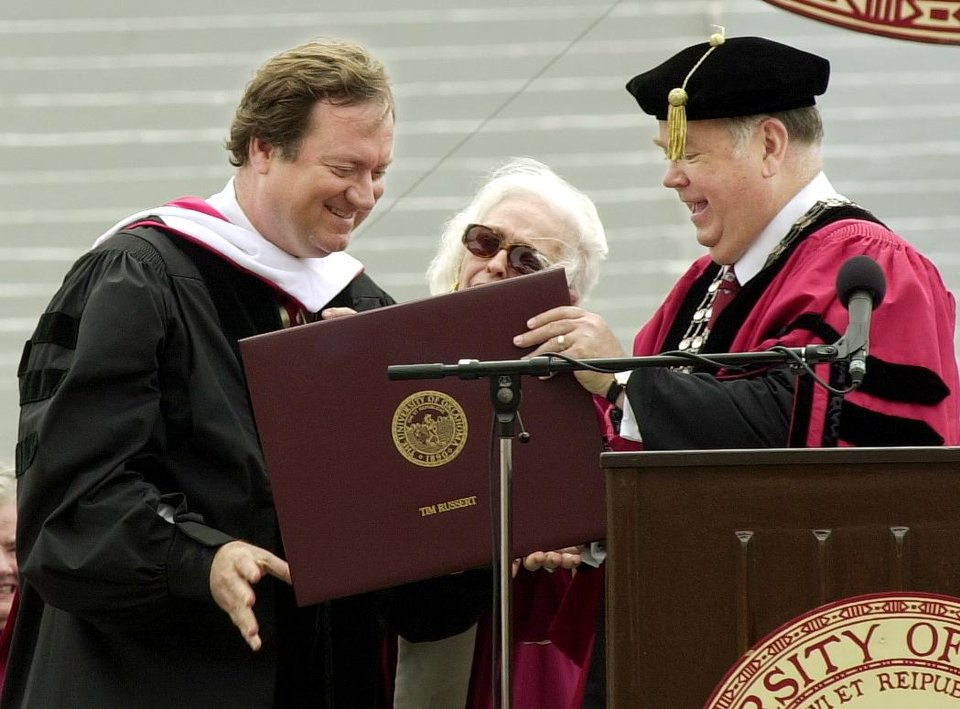 Photo - Guest speaker Tim Russert (left) receives an honorary degree from University of Oklahoma President David Boren at the OU graduation ceremony at Memorial Stadium Saturday morning in Norman. Staff photo by Ty Russell