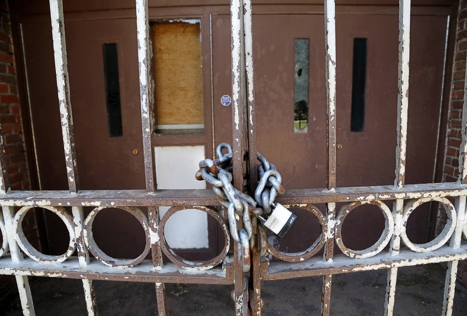 Photo -  Gates are locked at Dunbar Elementary School at 1432 NE 7, which sits empty and damaged by arsonists and other vandals. [Photo by Jim Beckel, The Oklahoman Archives]