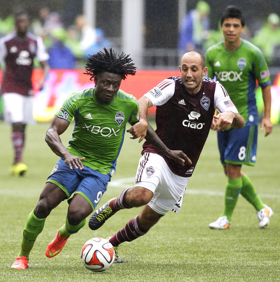 Photo - Seattle Sounders' Obafemi Martins, left, dribbles the ball around Colorado Rapids' Nick LaBrocca, right, in the second half of an MLS soccer match, Saturday, Aug. 30, 2014, in Seattle. The Sounders beat the Rapids, 1-0. (AP Photo/Ted S. Warren)