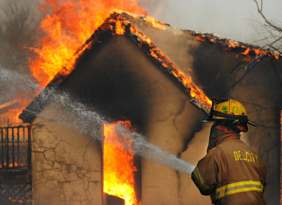 Photo - Del City firefighter Jerimiah Hoffstatter fights a house fire in the area of NE 23rd and Dobbs near Harrah Friday, March 11, 2011. Photo by Jim Beckel, The Oklahoman