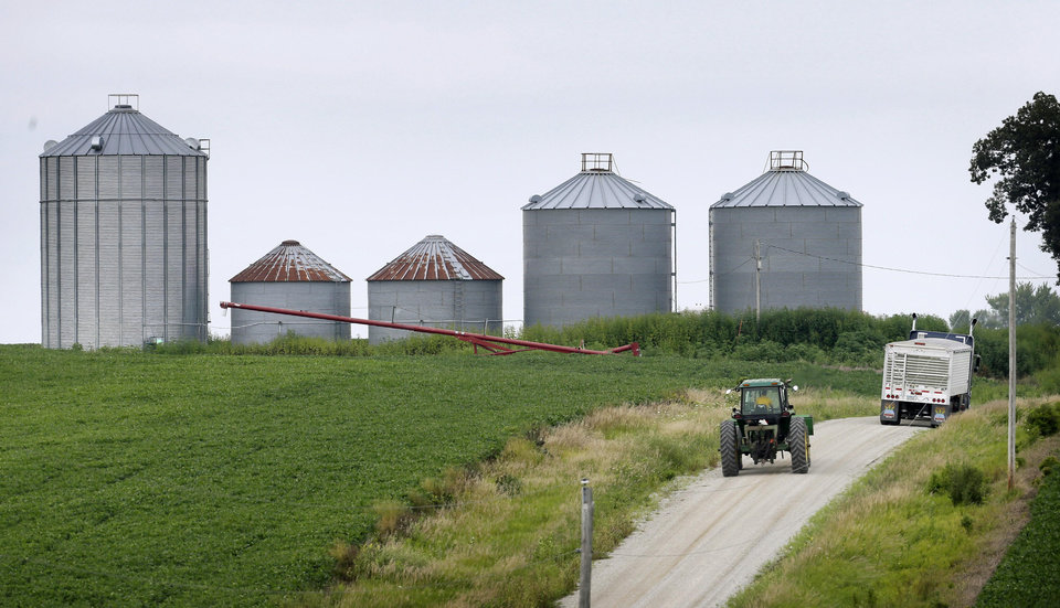 Photo - In this Aug. 5, 2014 photo a farmer drives his tractor past a soybean field toward grain storage bins near Ladora, Iowa. The nation's corn and soybean farmers are on track to produce record crops this year as a mild summer has provided optimum growing conditions. (AP Photo/Charlie Neibergall)