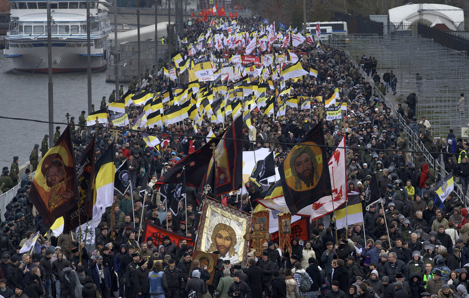 Photo -   Ultra nationalist demonstrators and activists march carrying the Russian Empire's black-yellow-white flags to mark National Unity Day, on the outskirts of Moscow, Sunday, Nov. 4, 2012. Chanting