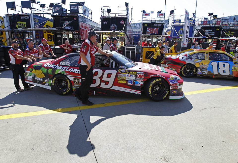 Photo -   Crew members push the cars of Ryan Newman (38) and Kyle Busch (18) from the garage before practice for Saturday's NASCAR Bank of America 500 Sprint Cup series auto race in Concord, N.C., Friday, Oct. 12, 2012. (AP Photo/Chuck Burton)