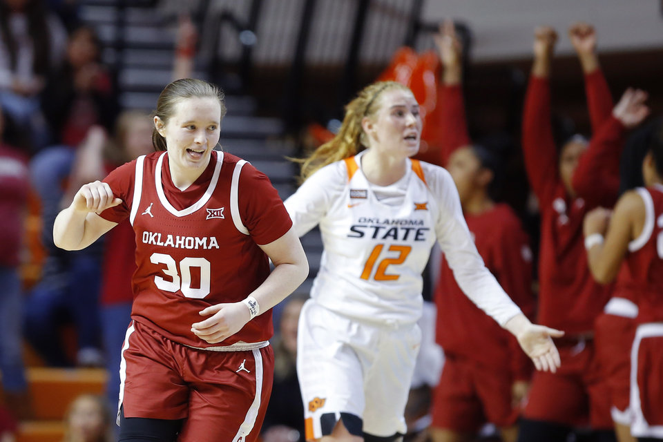 Photo - Oklahoma's Taylor Robertson (30) smiles in front of Oklahoma State's Vivian Gray (12) after making a basket during a women's Bedlam college basketball game between the Oklahoma State University Cowgirls (OSU) and the University of Oklahoma Sooners (OU) at Gallagher-Iba Arena in Stillwater, Okla., Wednesday, Jan. 8, 2020. [Bryan Terry/The Oklahoman]