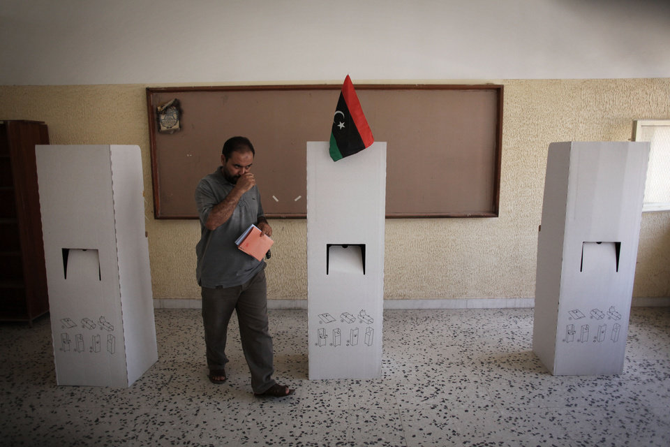 Photo -   A Libyan man leaves a voting booth to cast his ballot at a polling station in the former loyalist stronghold district of Abu Salim in Tripoli, Libya, Saturday, July 7, 2012. Jubilant Libyans marked a major step toward democracy after decades of erratic one-man rule, voting Saturday in the first parliamentary election after last year's overthrow and killing of longtime dictator Moammar Gadhafi. But the joy over the historic vote was tempered by boycott calls, the burning of ballots and other violence in Libya's restive east.(AP Photo/Manu Brabo)