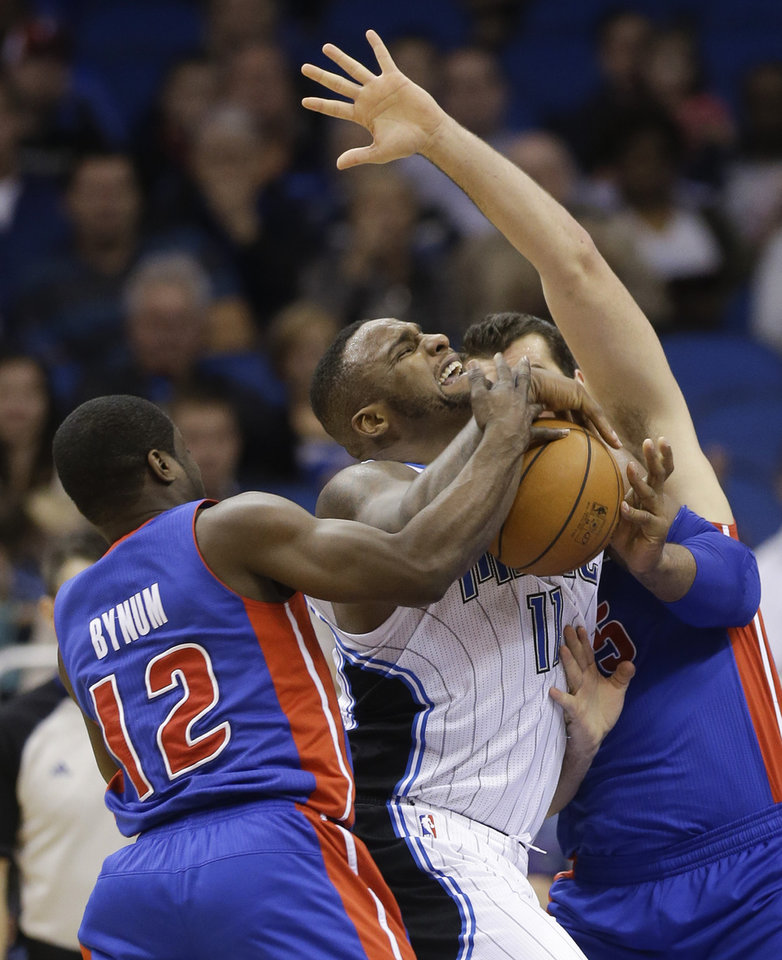 Photo - Orlando Magic's Glen Davis, center, pushes his way past Detroit Pistons' Will Bynum (12) and Josh Harrellson, right, as he makes a move to the basket during the first half of an NBA basketball game in Orlando, Fla., Friday, Dec. 27, 2013. (AP Photo/John Raoux)